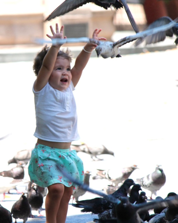 A little girl scares away the pigeons.
